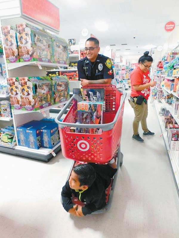 Five-year-old Elicah Saito Campbell rides on the bottom of a shopping cart steered by police traffic officer Justin Mauliola while looking for toys Sunday morning.