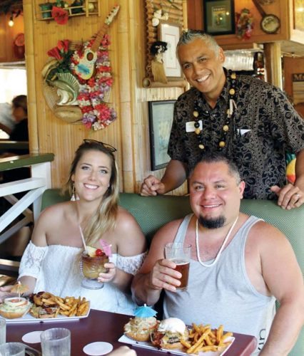 Cheeseburger Grille & Tap Room  General Manager Kristopher Galon (standing) takes care of Cheyenne Walker and Raul Arellano, visitors from Mt. Vernon, Wash., as they sip a Mai Tai and a cold beer over a big lunch in Wailea recently. The Maui News / CARLA TRACY photos