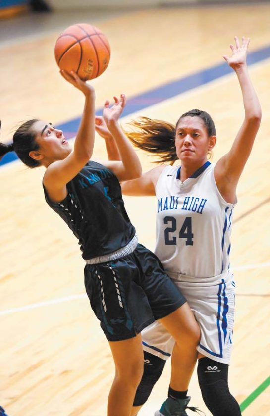 King Kekaulike High School's Charlie Abreu shoots against Maui High's Kamaile Cugal during the second quarter of Na Alii's 52-46 victory over the Sabers on Wednesday night. The Maui News / MATTHEW THAYER photo