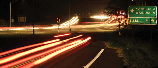 Lights of traffic on Hana Highway and Hansen Road are blurred in this time-lapse photo taken Thursday evening from the side of Hansen Road in Kahului. The Maui Metropolitan Planning Organization is calling on the Maui County Council to adopt a 0.5 percent increase in the general excise tax to jump-start needed state transportation highway projects. -- The Maui News / MATTHEW THAYER photo