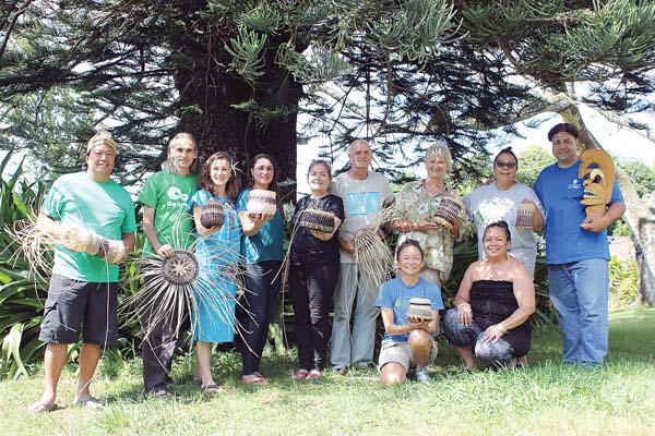 Lloyd Kumula'au Sing Jr.(far right holding  tiki) and May Haunani Balino-Sing (kneeling front in black top) with participants in a Hawaiian basketry class. -- Photo courtesy Hui No'eau