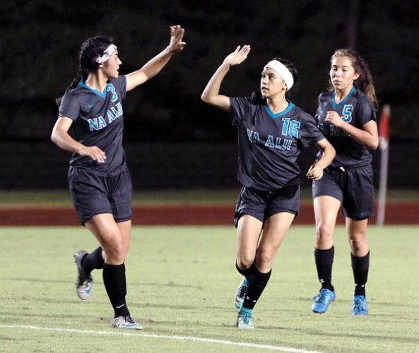 Erynn Duquette (center) of King Kekaulike High School high-fives Zoe Asue next to Nyasia Martinez after scoring a goal in the first half Friday. -- The Maui News / CHRIS SUGIDONO photo