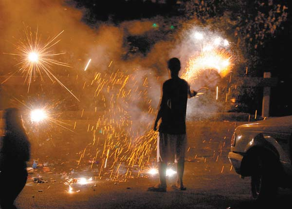 People celebrate New Year's Eve 2010 with sparklers. The sale of fireworks begins Dec. 26. Firecracker permit sales begin today, according to the Maui Fire Department. The Maui News file photo