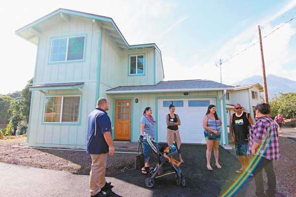 Kiha Coelho (from left), Tiana Donato and son, Serge Coelho, hang out in front of their new home with Donato's sister Brandi Donato, parents Cindy and Joe Donato and Cindy Texeira of Lokahi Pacific.