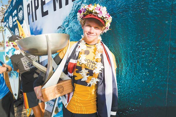 John John Florence of Oahu poses with his trophy after clinching the World Surf League Championship Tour title for the second year in a row Monday. World Surf League / KELLY CESTARI photo