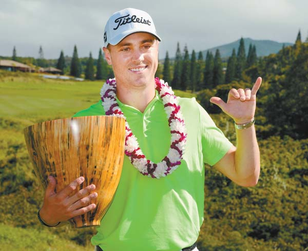 Justin Thomas poses with his trophies from the Tournament of Champions