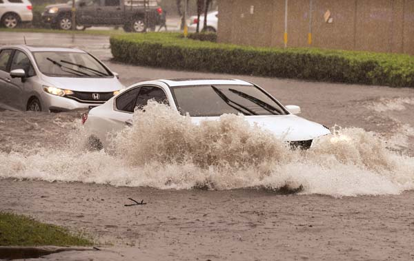 Two of the last cars to navigate Dairy Road before it was closed by Maui police officers plow through the flooded roadway Wednesday morning.