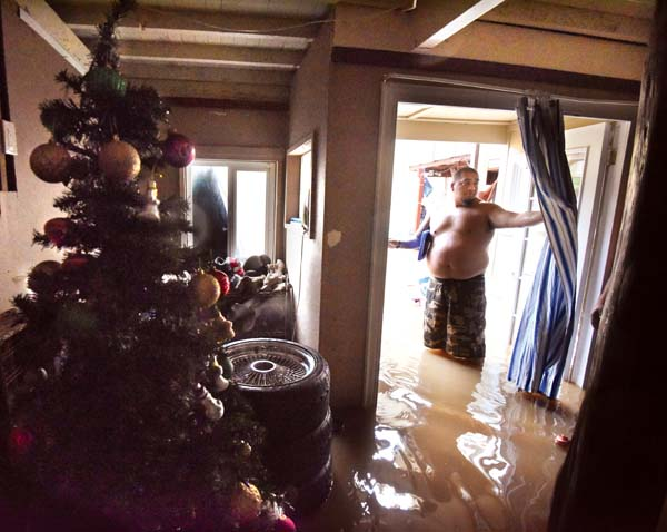 Happy Valley resident Hinano Nelson surveys the brown, knee-deep water in his living room and the ruined Christmas presents and decorations Wednesday morning. The Maui News MATTHEW THAYER photos