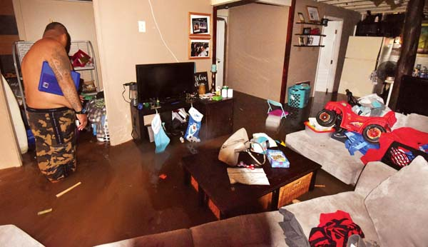 Happy Valley resident Hinano Nelson wades through his flooded home Wednesday.