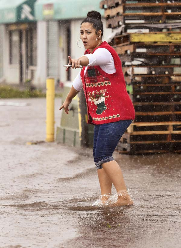 Marmac Ace Hardware store manager Kaysha Kekiwi stops a motorist from driving over a curb while trying to turn around on Kahului's flooded Lalo Street on Wednesday morning. Kekiwi was one of the last employees to leave the store after it was closed due to flooding. She helped the driver find an entrance to the store parking lot and avoid Lalo where at least one car was stranded.
