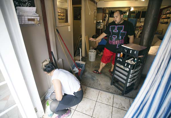 Friends Arthur Kaleikini and Carlene DelaCruz on Thursday help clean a Happy Valley residence that was damaged by floodwaters. Four people were displaced in the home, as well as six others in a neighboring unit. The Maui News / CHRIS SUGIDONO photo