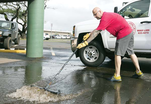 John Truselo, backyard manager of Marmac Ace Hardware in Kahului, pushes water Thursday morning toward a pump to drain the store's parking lot that was flooded by Wednesday's downpour. The Maui News / CHRIS SUGIDONO photo