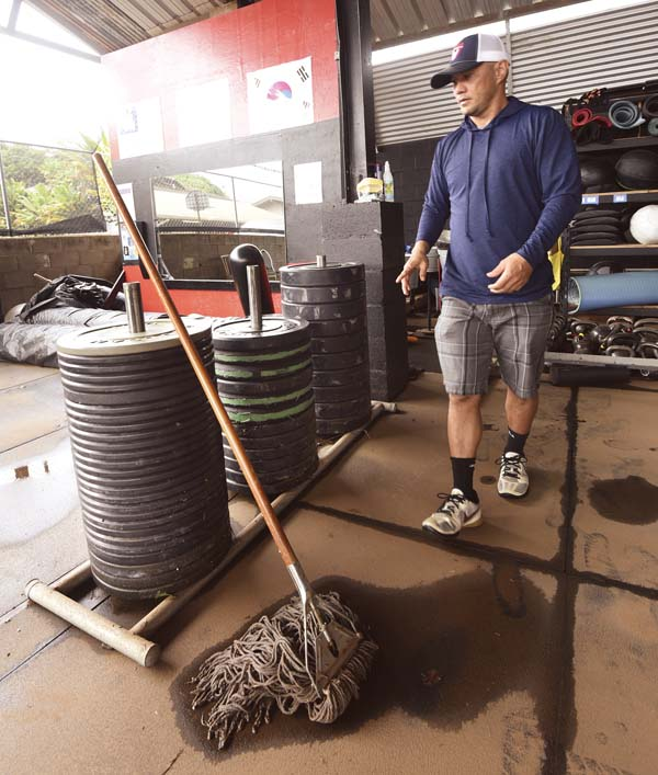 Vernon Patao passes racks of weights as he surveys damage to his equipment Thursday.  The Maui News / MATTHEW THAYER photo