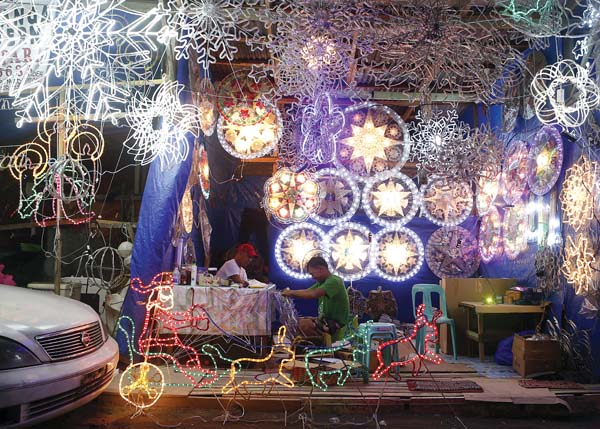 """Lantern makers work on traditional Christmas lanterns known as """"parols"""" in a side-street shop in Manila. -- AP photo"""