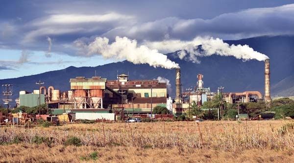 Smoke and steam rise from the Puunene Mill's smokestacks in September 2016. Now, much of the mill equipment has been sold at auctions. A&B plans to sell remaining equipment and repurpose or disassemble the remaining structures. - The Maui News / MATTHEW THAYER photo
