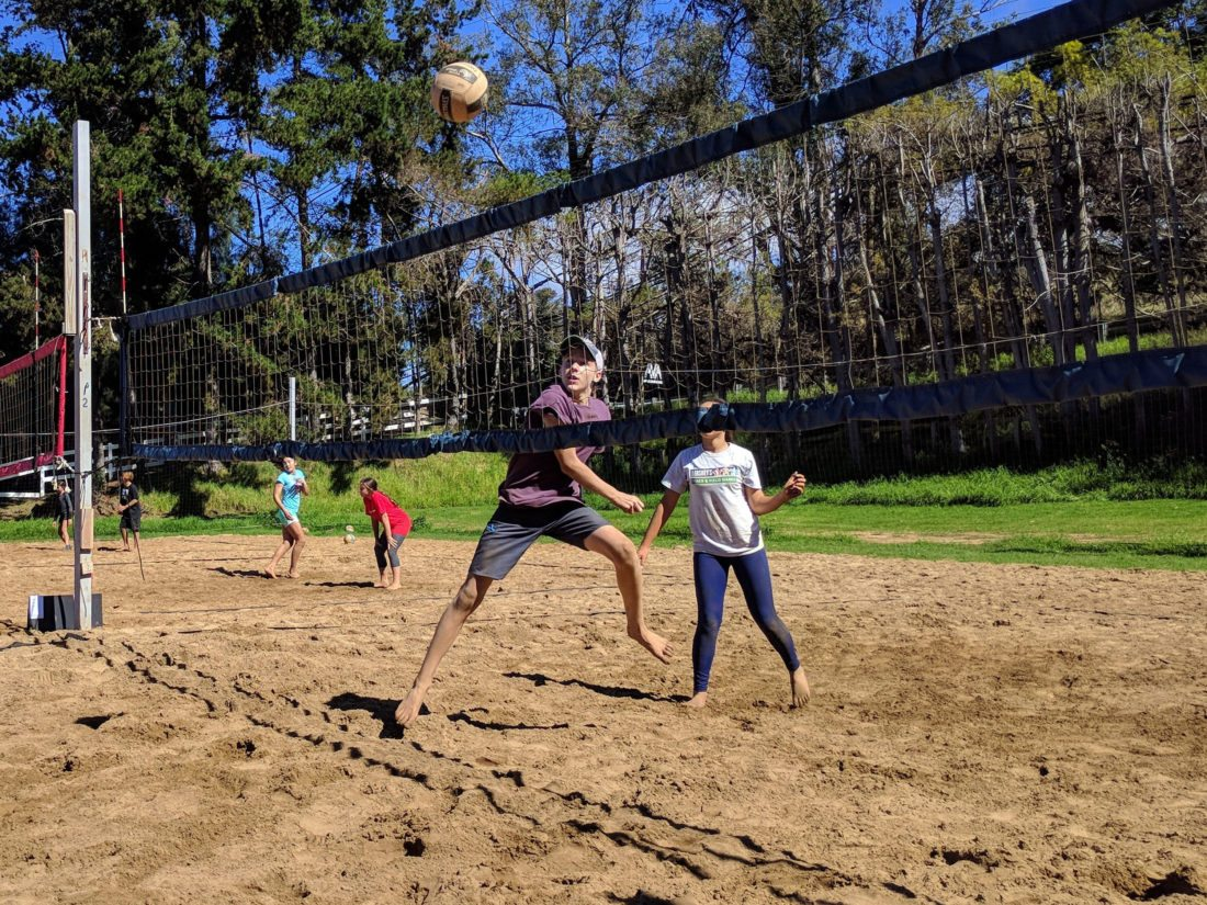 FIRST PHOTO: Thomas Russell contorts his body to get a ball over the net as Emeli Hay-Muagututia looks on during Aloha Volleyball's 14s King of the Beach tournament Wednesday in Kula. Russell won the event. • SCOTTIE ZUCCO photo