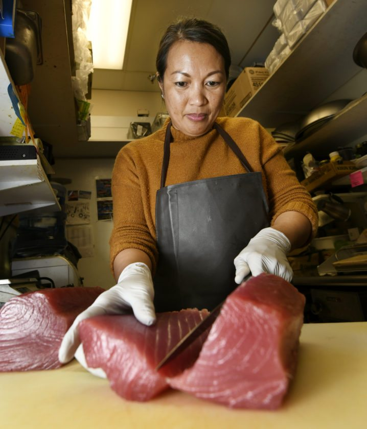 Oki's Seafood owner Elisa Garcia cuts sashimi on Thursday afternoon in her busy shop located inside Foodland Kaahumanu.  Local fish retailers predict there should be enough fish available for customers for their New Year's holiday celebrations. • The Maui News  MATTHEW THAYER photo