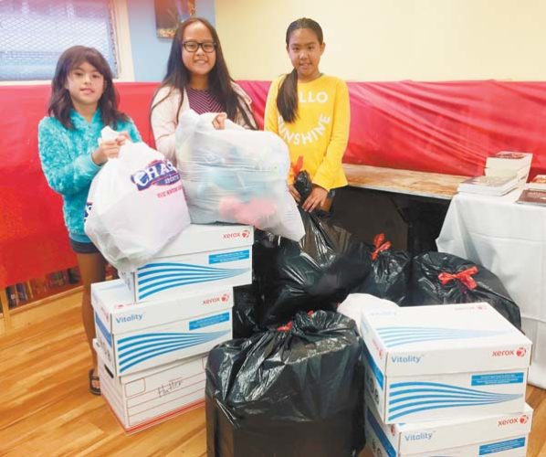 Kihei Elementary School Student Council Members Maya Connolly (from left), Lyric AhPuk and Ava Arai display the bags and boxes full of donated toys for children who receive support from Maui Family Support Services.