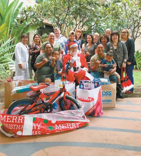 The Rodrigues family received Christmas gifts from Maui Memorial Medical Center through Maui Family Support Services Adopt-A-Family program. Pictured with members of the family are hospital staff members.