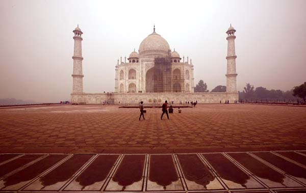 Tourists walk around the Taj Mahal as workers clean the monument in Agra, India, on Dec. 5. Travel guidebook publisher Fodor's has published a list of where not to go in 2018 that includes the Taj Mahal. -- AP photo