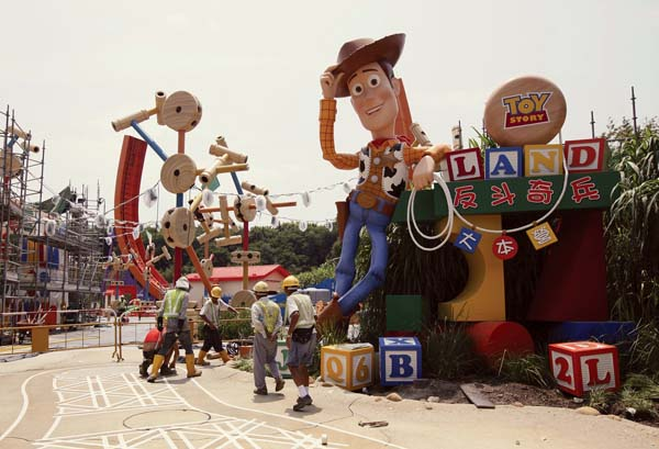 "Workers walk past ""Toy Story"" character Woody at the construction site of Toy Story Land at Hong Kong Disneyland in 2011. A new 11-acre Toy Story Land is expected to open in 2018 at Walt Disney World Resort near Orlando, Fla. -- AP file photo"