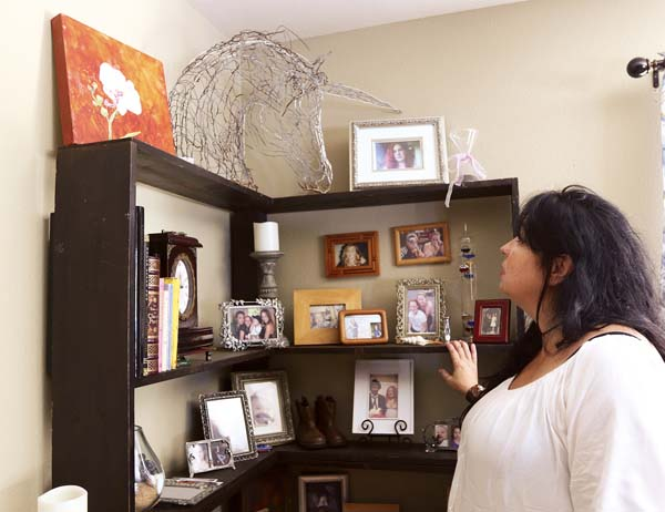 "Kimberlyn Scott looks at a shelf of photos, personal items and other mementos of her murdered daughter, Carly ""Charli"" Scott, on Wednesday morning at her friend's house in Kihei. -- The Maui News / CHRIS SUGIDONO photo"