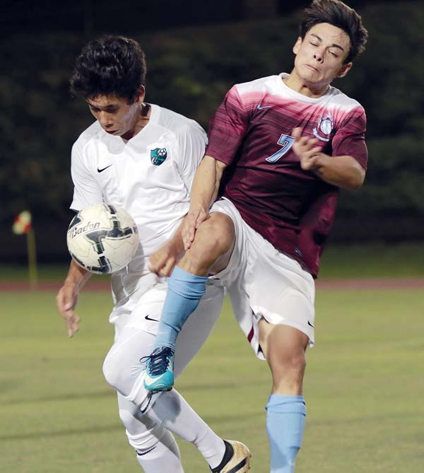 Baldwin's Angelo Deloso Flocco and King Kekaulike's Ty Miller battle vie for a ball during the second half of a 1-1 draw in the boys match. - The Maui News / CHRIS SUGIDONO photo