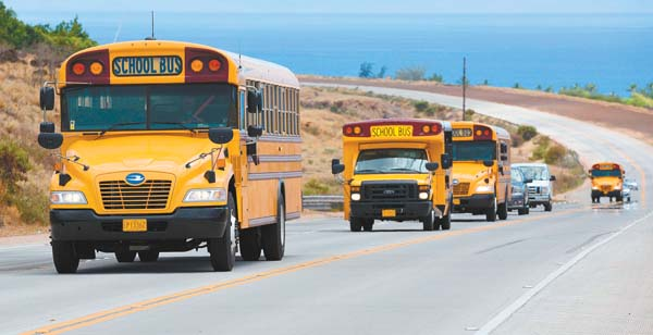 A caravan of Ground Transport school buses motors along the Lahaina bypass Sept. 8 as the end of the school day approaches. Due to a bus driver shortage, most school bus routes for Lahainaluna High School were suspended at the beginning of the school year in August. By September, new drivers had been hired and bus routes were restored. The Maui News / MATTHEW THAYER photo