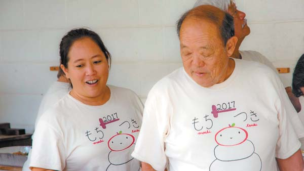 Lyndra Okamoto and her father, Tom Fujita, watch as mochi is pounded and shaped last month. ASA ELLISON photo