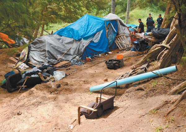 Law enforcement officers work to clear away a homeless encampment at Baldwin Beach Park on May 23. The Maui News / MATTHEW THAYER photo