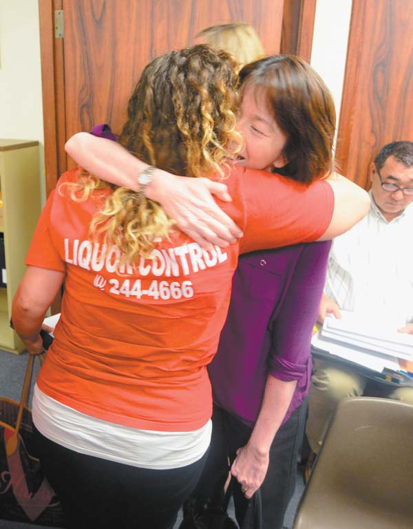 Mahina Martin (right) is hugged by Ashlee Chapman after the Maui County Liquor Control Commission's July 12 decision to reverse its controversial liquor rule changes made earlier in the year. The panel voted to reinstate the 11 p.m.-to-6 a.m. blackout on retail liquor sales and the cap of 12 hostess bars in the county. The Maui News / MATTHEW THAYER photo