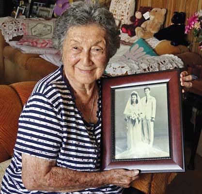 Violet Komoda is shown holding a photo from her wedding to husband Joe Kazuo Komoda.