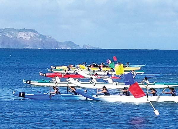 Paddlers take off from the starting line in the girls varsity race Saturday at Kahului Harbor. -- MAHINA MARTIN photo