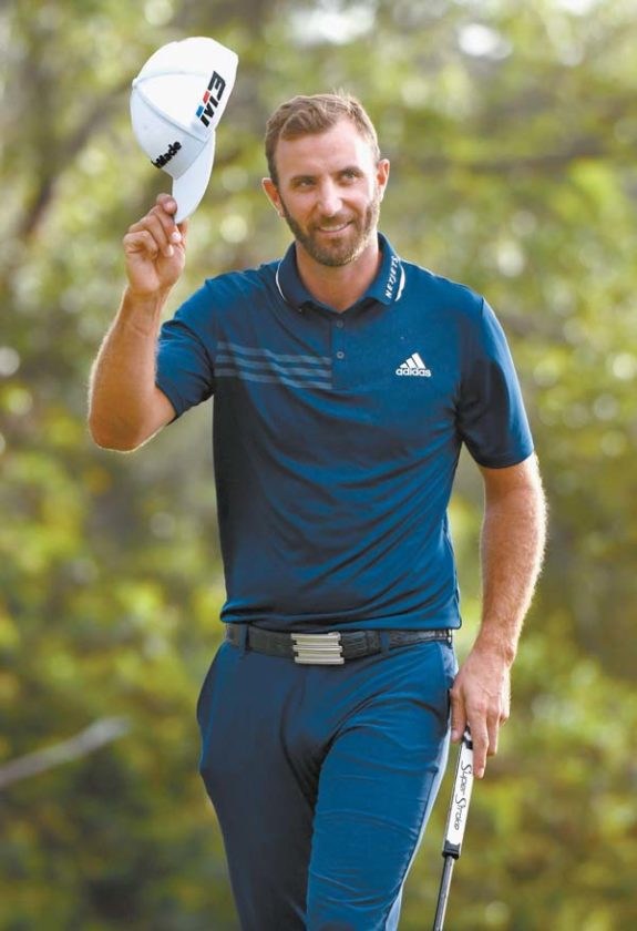 Dustin Johnson doffs his cap to acknowledge the gallery on the Kapalua Plantation Course's 18th green Sunday after sinking his final putt to win the Sentry Tournament of Champions with a 24-under-par total of 268. The Maui News / MATTHEW THAYER photos