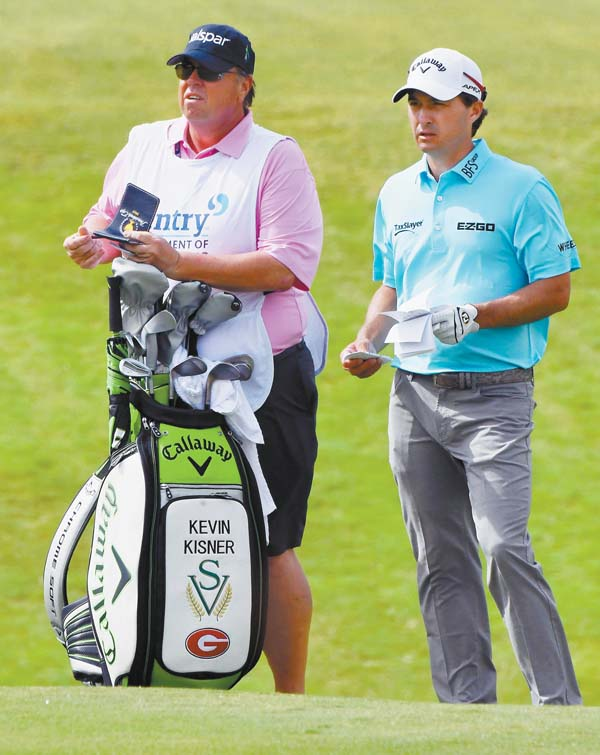 Kevin Kisner sports a Georgia logo on his bag as he and caddie Duane Bock prepare for a shot on the ninth hole Sunday. The Maui News MATTHEW THAYER photos