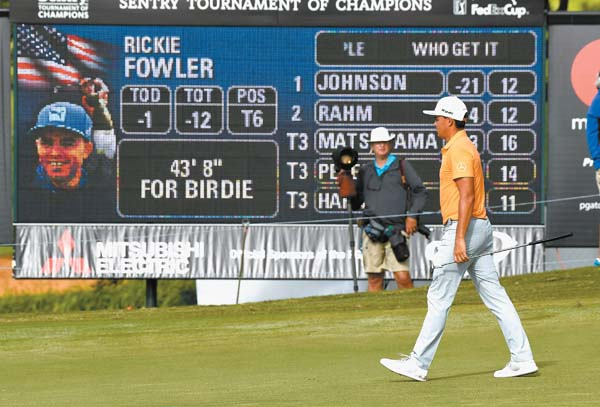 Rickie Fowler walks in front of a scoreboard on the 13th green.