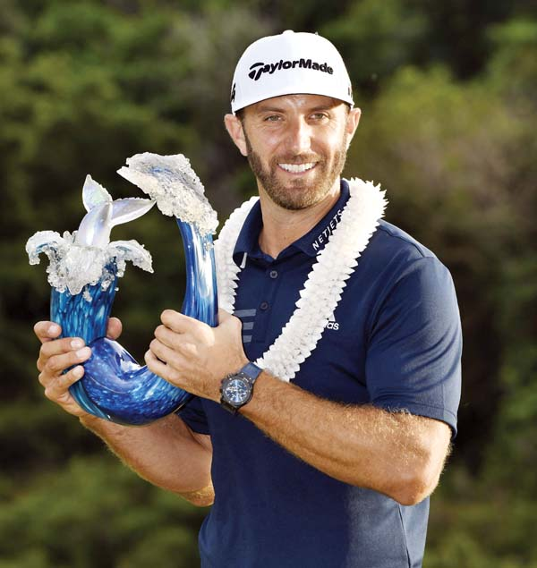 Dustin Johnson, who captured the Sentry Tournament of Champions by eight strokes, holds the tournament trophy on Sunday at Kapalua.