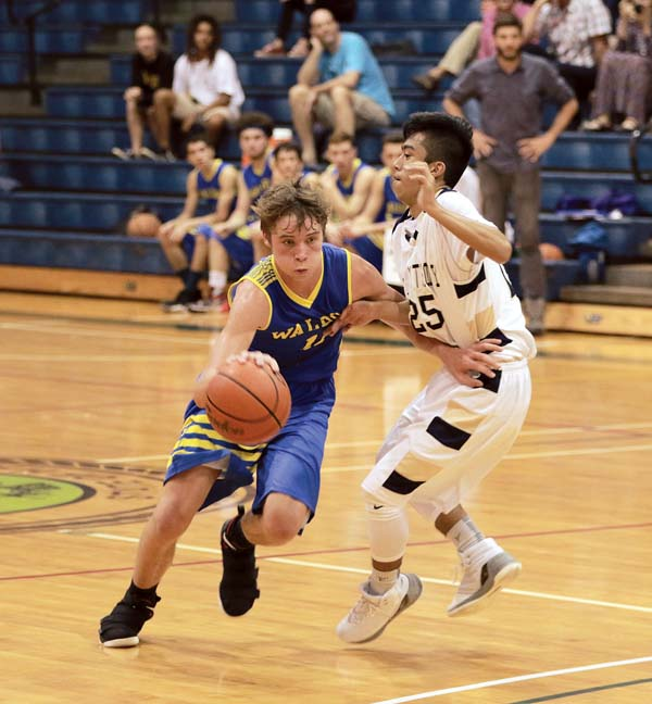 The Rays' Patrick Doster drives to the basket on the Trojans' Nate Rabara in the second quarter. - The Maui News / CHRIS SUGIDONO photo