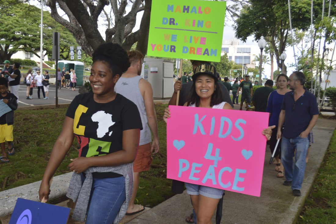 Chrissy Tabb (left) and Jodi Komine were some of the estimated several hundred attendees at the Dr. Martin Luther King Jr. Peace March at the Kalana O Maui building Monday morning. Tabb said the gathering of various races and backgrounds showed that the slain civil rights leader's dream  endures. • The Maui News / MELISSA TANJI photo