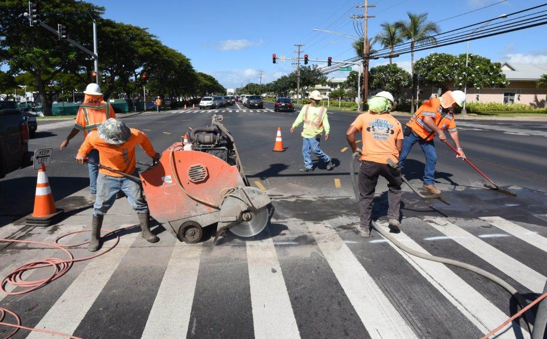 Workers for Lite Electric use a powerful saw to make a pair of cuts across Honoapiilani Highway at the intersection with Keawe Street on Tuesday afternoon. The cuts are for a trench that is to be dug across the highway for utilities to be installed. Residents complain that the changes to the intersection will create more congestion and safety hazards. • The Maui News / MATTHEW THAYER photo