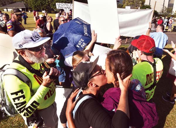 """In response to Alex Hall's rant against homosexuality, two young women, Faith Lindstrom and Mitch Ray, embrace for a long kiss while standing between the Halls. Ray said the Halls have a right to say what they want. """"It doesn't bother us,"""" she said. - The Maui News / MATTHEW THAYER photo"""