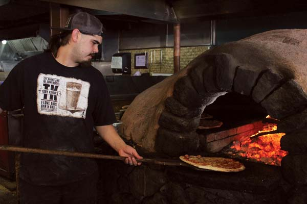 Kimo Beezley (in photo) works the oven at Flatbread Company and then the pizza is sliced (second photo). The Maui News / CARLA TRACY photos