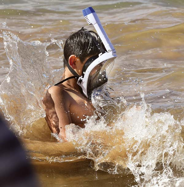 Tristen Grey, 12, of Saskatchewan, Canada, is jostled by a wave while entering the water at Kamaole III Beach Park. He is snorkeling with a full-face mask. He said he was having no problems with it. Some are questioning the safety of the mask's design, saying it's prone to leaking and fogging up and can be difficult to take off. Two California men died recently while snorkeling in the ocean off Kihei, and both were using the new type of masks. More recent deaths, however, have involved snorkelers using traditional two-piece snorkel-and-mask equipment. -- The Maui News / MATTHEW THAYER photo