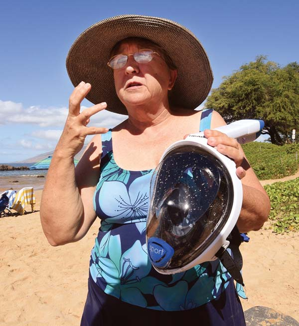 """San Diego visitor Chris Houkom holds another beachgoer's full-face mask while describing why she ditched hers after only a few tries. """"I gave it away,"""" she said. """"I wasn't as relaxed. It felt like I was breathing hot air."""" -- The Maui News / MATTHEW THAYER photo"""