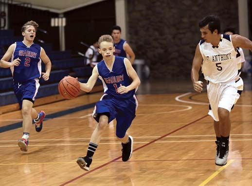 Seabury Hall's Noah Payne dribbles next to Carl Molinaro and St. Anthony's Jake Gage in the first quarter of the Spartans' 51-15 victory over the Trojans on Friday. -- The Maui News / CHRIS SUGIDONO photo