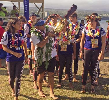 Seabury Hall coach Paul Luuwai holds the championship trophy after the Spartans won the mixed race Saturday at the state regatta at Hilo Bay. -- Hawaii Tribune- Herald / MATT GERHART photo