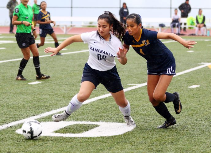 Brynn Rodrigues of Kamehameha Schools Maui fights Waipahu's Kaycee Manding for the ball in the first half of the Warriors' 1-0 overtime victory over the Marauders in a state tournament first-round match Monday afternoon at Kanaiaupuni Stadium. • The Maui News / CHRIS SUGIDONO photo