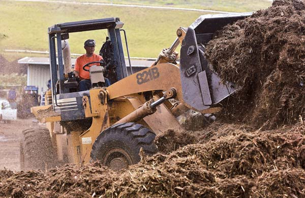 Maui EKO Systems utility operator David Gamurot operates a front loader to move green waste turned to mulch Tuesday afternoon at the Central Maui Landfill. The Maui News / CHRIS SUGIDONO photos