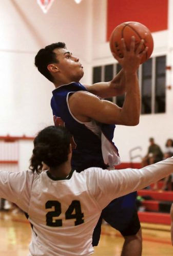 Seabury Hall's Isaiah Payne goes up for a shot against Lanai's Devrene Kahananui Alejado in the third quarter of the Spartans' 58-42 victory over the Pine Lads on Tuesday night at Lahainaluna. The Maui News / CHRIS SUGIDONO photos