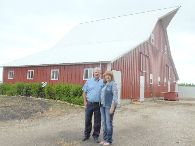 -Messenger photo by Lyn Vandebrake Richard and Marsha Adams pose by the red barn, one of two 100-year-old-plus barns on their farm.